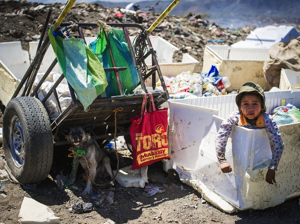 A little girl plays and waits for her mother while she sorts garbage inside Nueva Vida trash dump. Many children are raised in dump sites and that becomes their job from childhood. Ciudad Sandino, Nicaragua. Photo by: Timothy Bouldry, 2015.